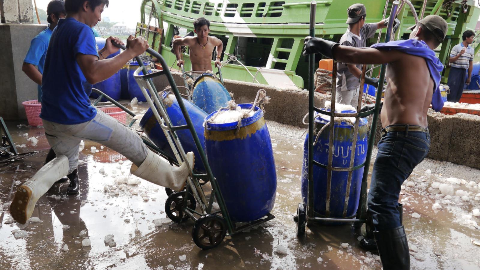 Dockworkers in Thailand load barrels onto a ship.