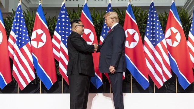 Donald trump and Kim Jong Un shanking hands in front of US and North Korean Flags