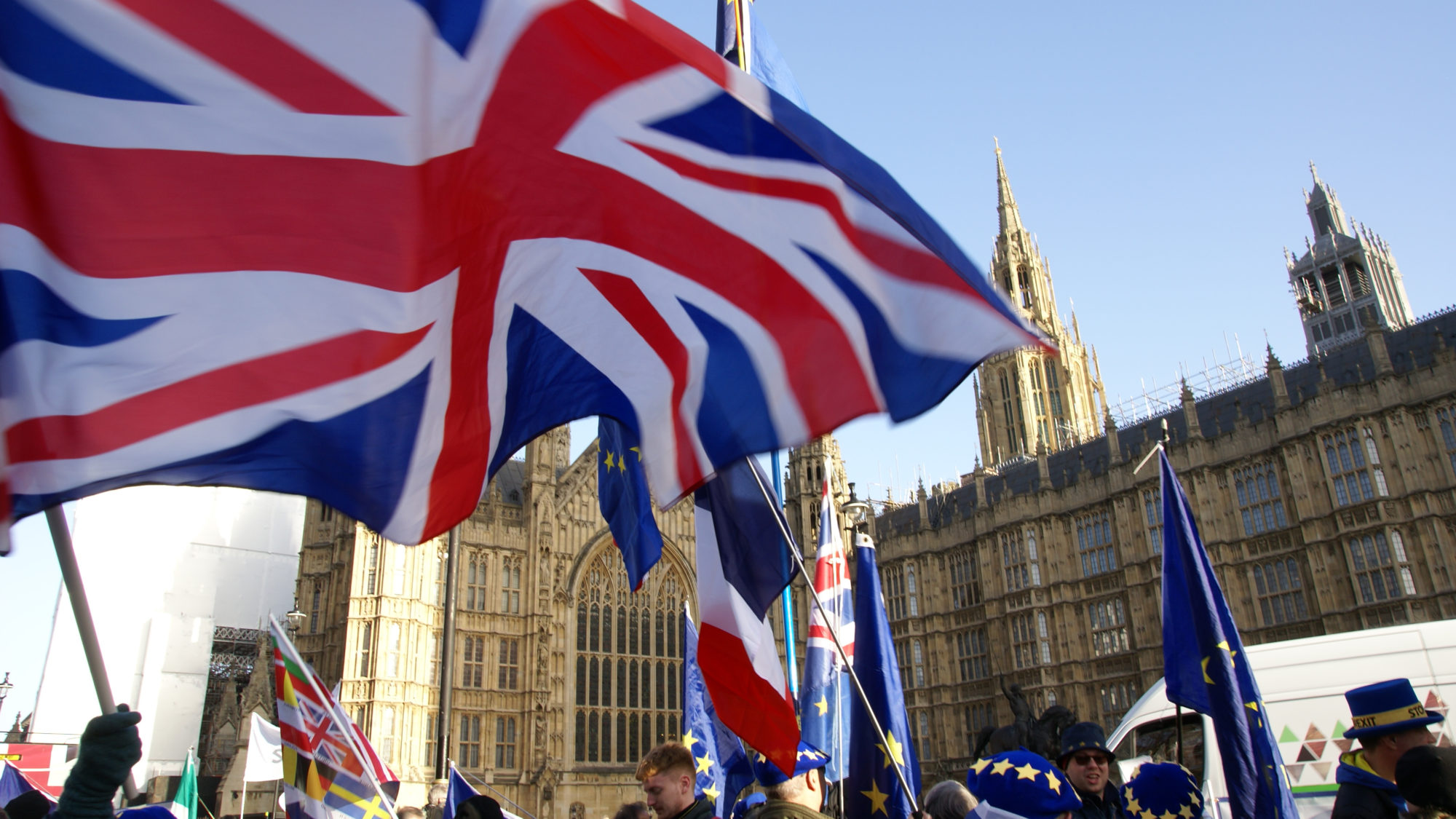 People stand with British and EU flags outside of Westminster Palace.