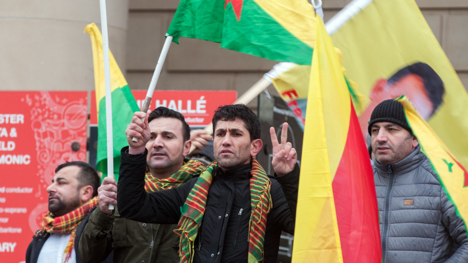 Four men holding Kurdish flags, participating in protest against Kurdish military aggression.