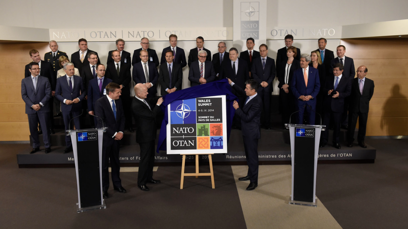 Leaders of NATO countries stand on a stage and look on as the Secretaries of State from the UK and Wales unveil the logo of the 2014 NATO Summit in Wales.