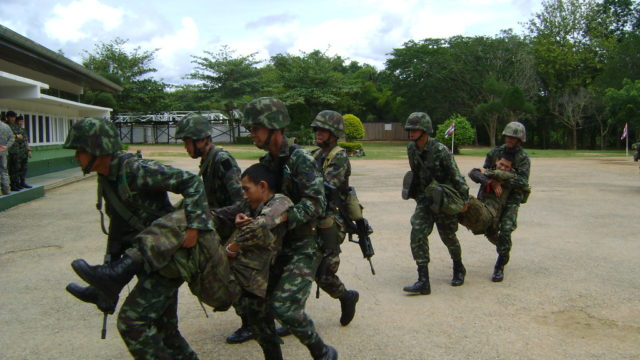 Thai soldiers practicing counterinsurgency training. Several men in Thai military uniform carrying another man in uniform.