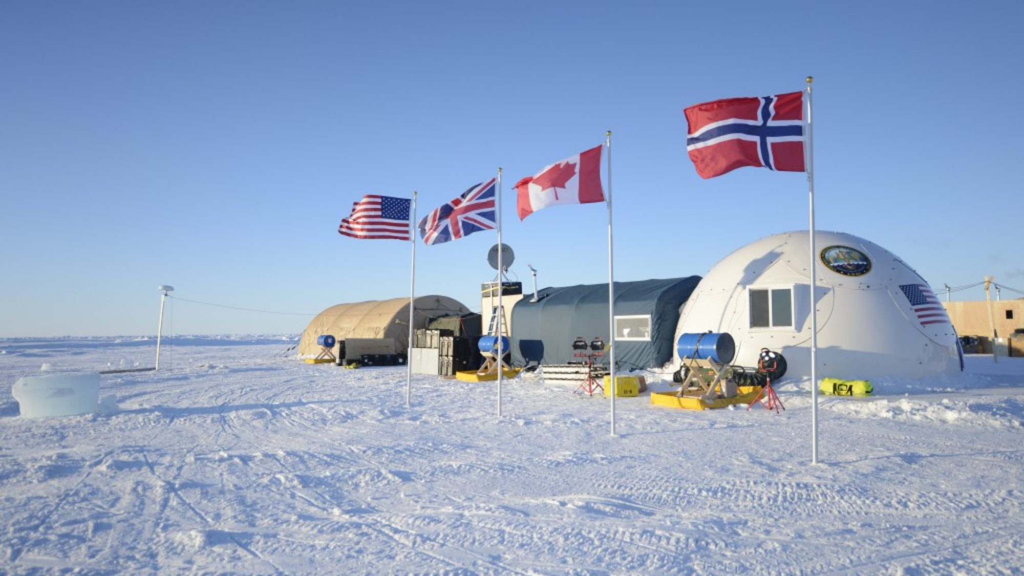 The flags of the U.S., the UK, Norway, and Canada are planted next to each other in the ice outside of a research station in the Arctic.