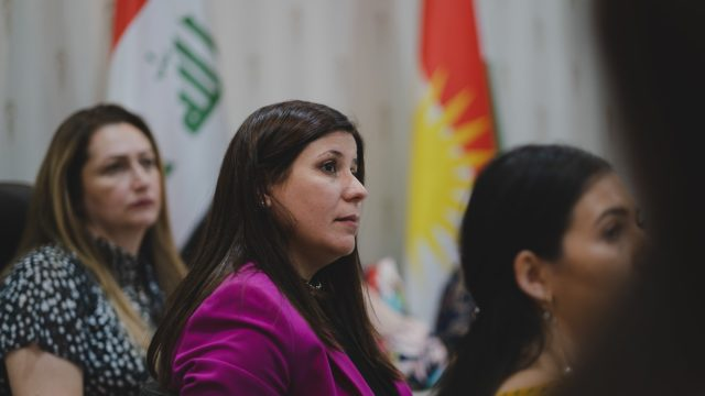 Florin Gorgis, a female human rights and women's rights activist, sits at a table looking into the distance. The flags of Kurdistan and Iraq are in the background.
