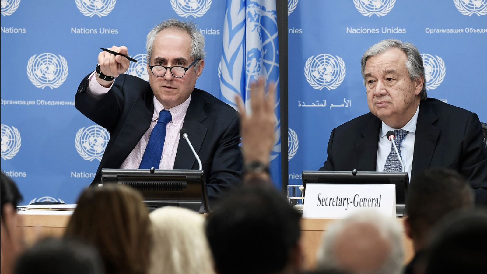 Stephane Dujarric and António Guterres take questions from a room of reporters.