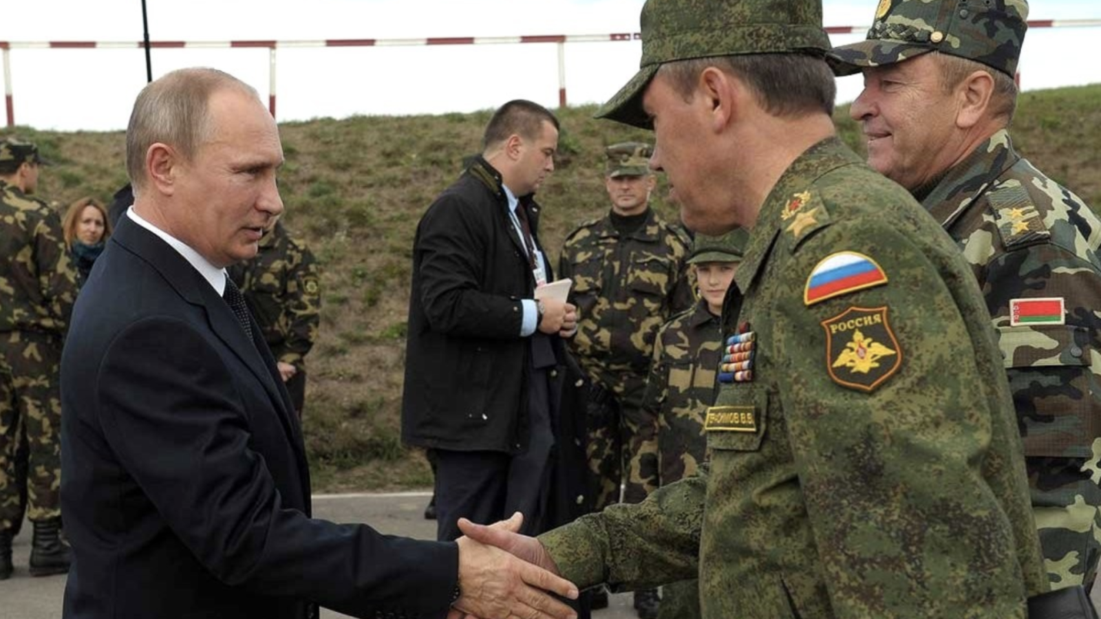 Vladimir Putin shakes the hand of a member of the Russian military.