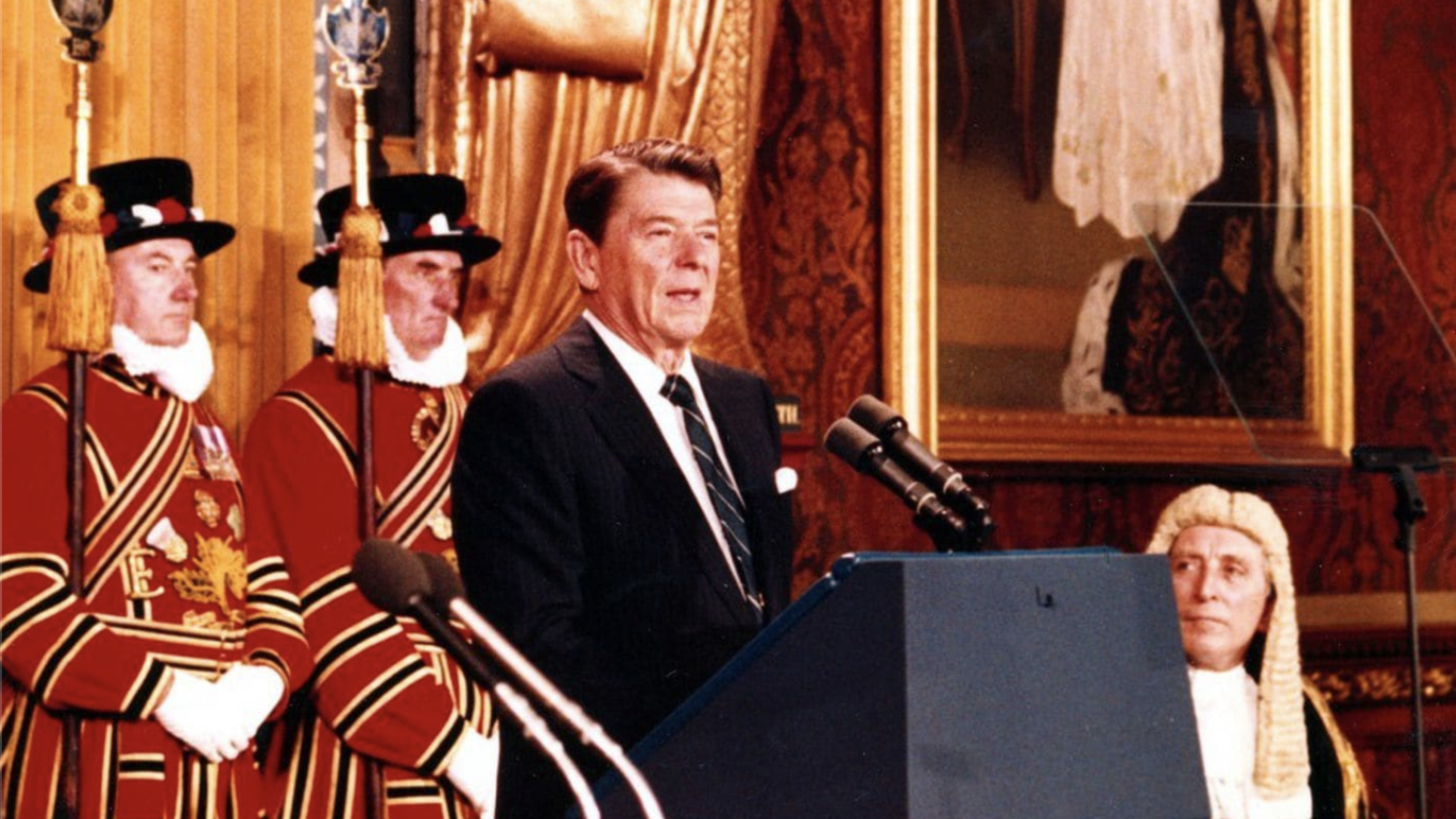 Ronald Reagan is standing at a podium and addresses the British parliament.