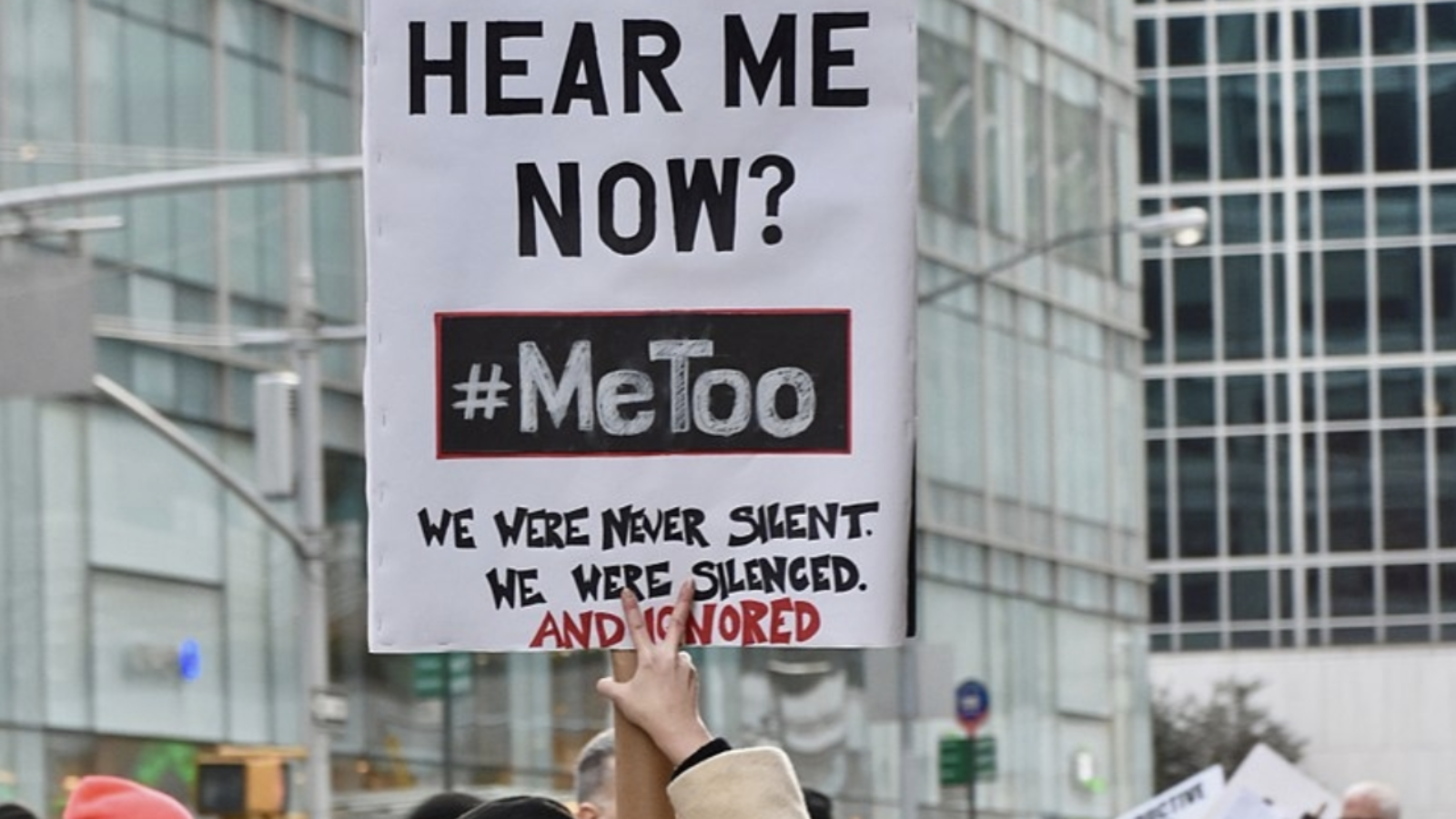A woman stands in a crowd of protestors holding a sign that reads,