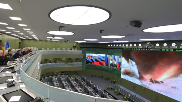 Members of the Russian Defense Ministry sit in a lecture hall watching an Avangard missile test launch on a screen