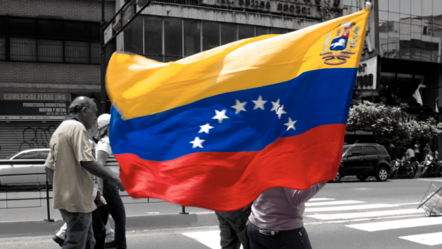 A person walks down the middle of a street carrying the Venezuelan flag.