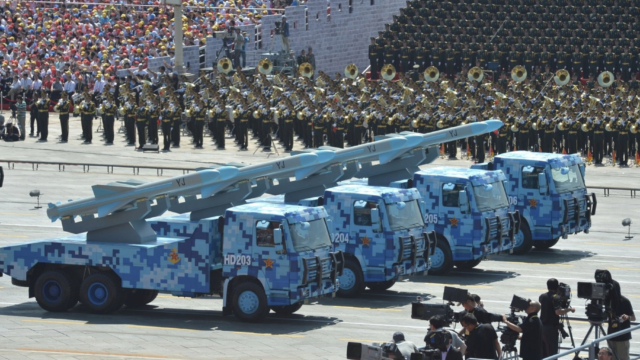 Four trucks carrying missiles marked YJ drive down the road as part of China's 70th National Day parade.