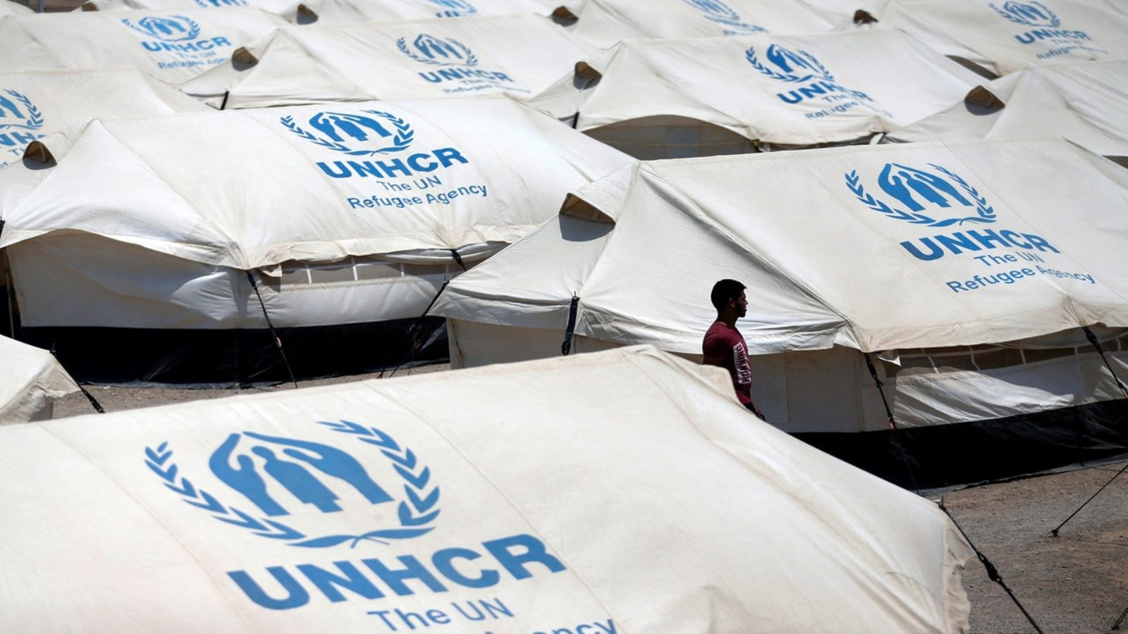 A man walks alone through a cluster of white tents with the UNHCR logo on them