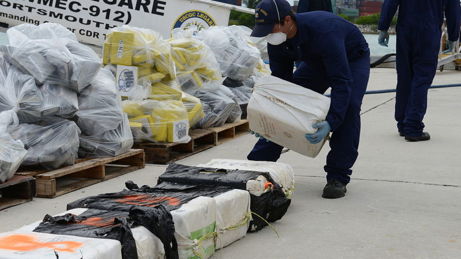 A U.S. Coast Guardsman assigned to the medium endurance cutter USCGC Legare (WMEC 912) stacks a bale of cocaine seized as part of Operation Martillo at Coast Guard Base Miami Beach, Fla.