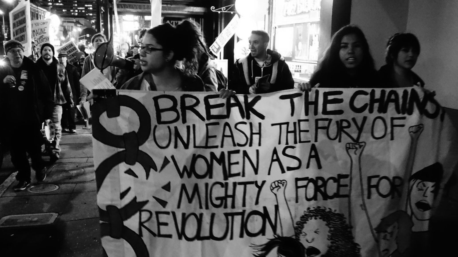 A group of women hold a sign that reads,