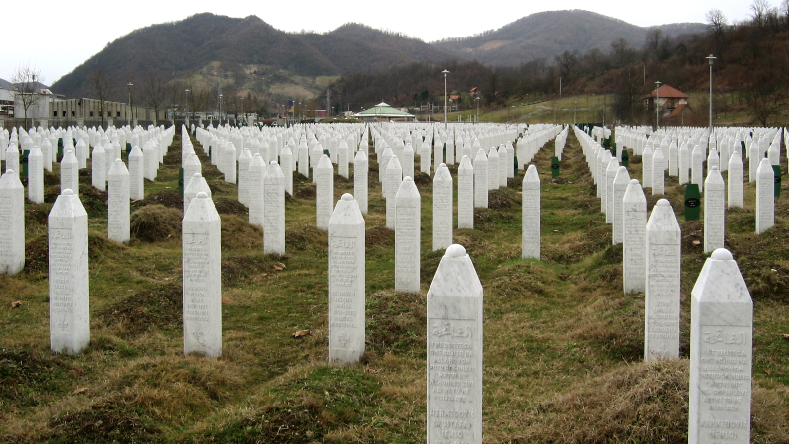 Rows of white, pillar-shaped gravestones are lined up in a field as part of a memorial to the Srebrenica genocide.