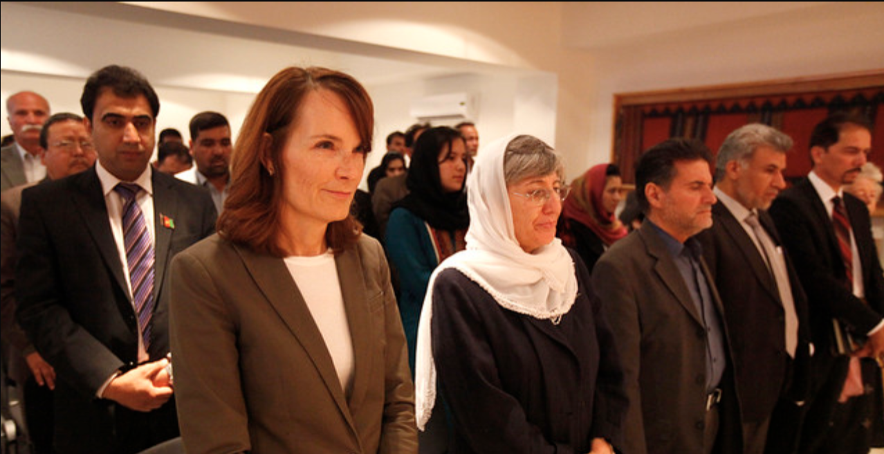 A group of people stand in rows with hands clasped, including Afghan officials and UN Afghanistan Human Rights Director.