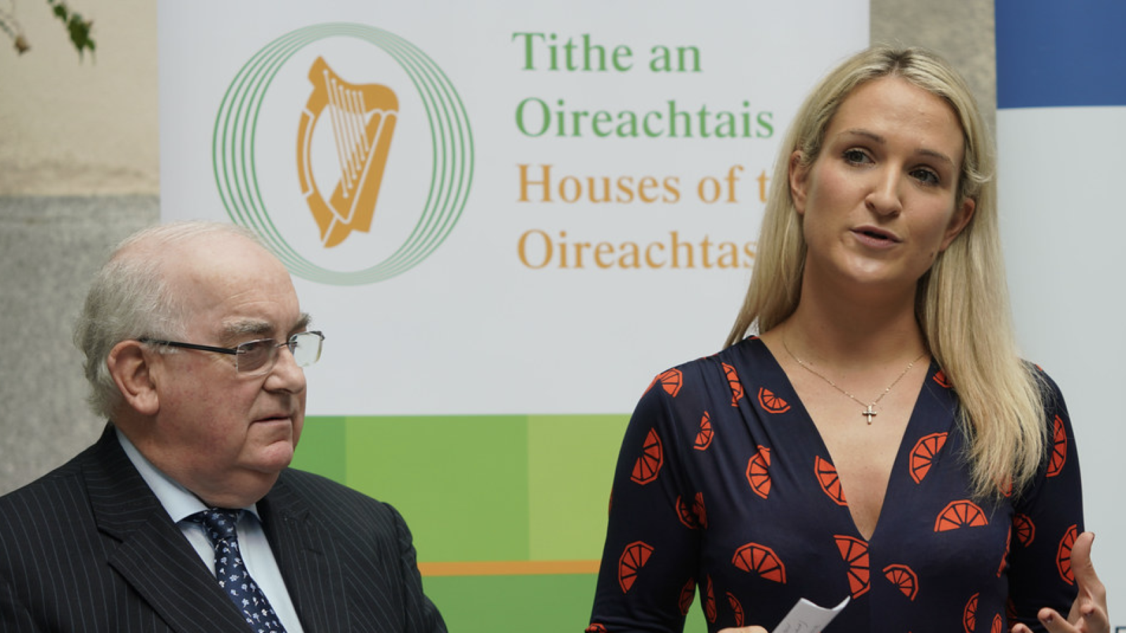 Helen McEntee stands on a stage talking, next to a male Irish official.
