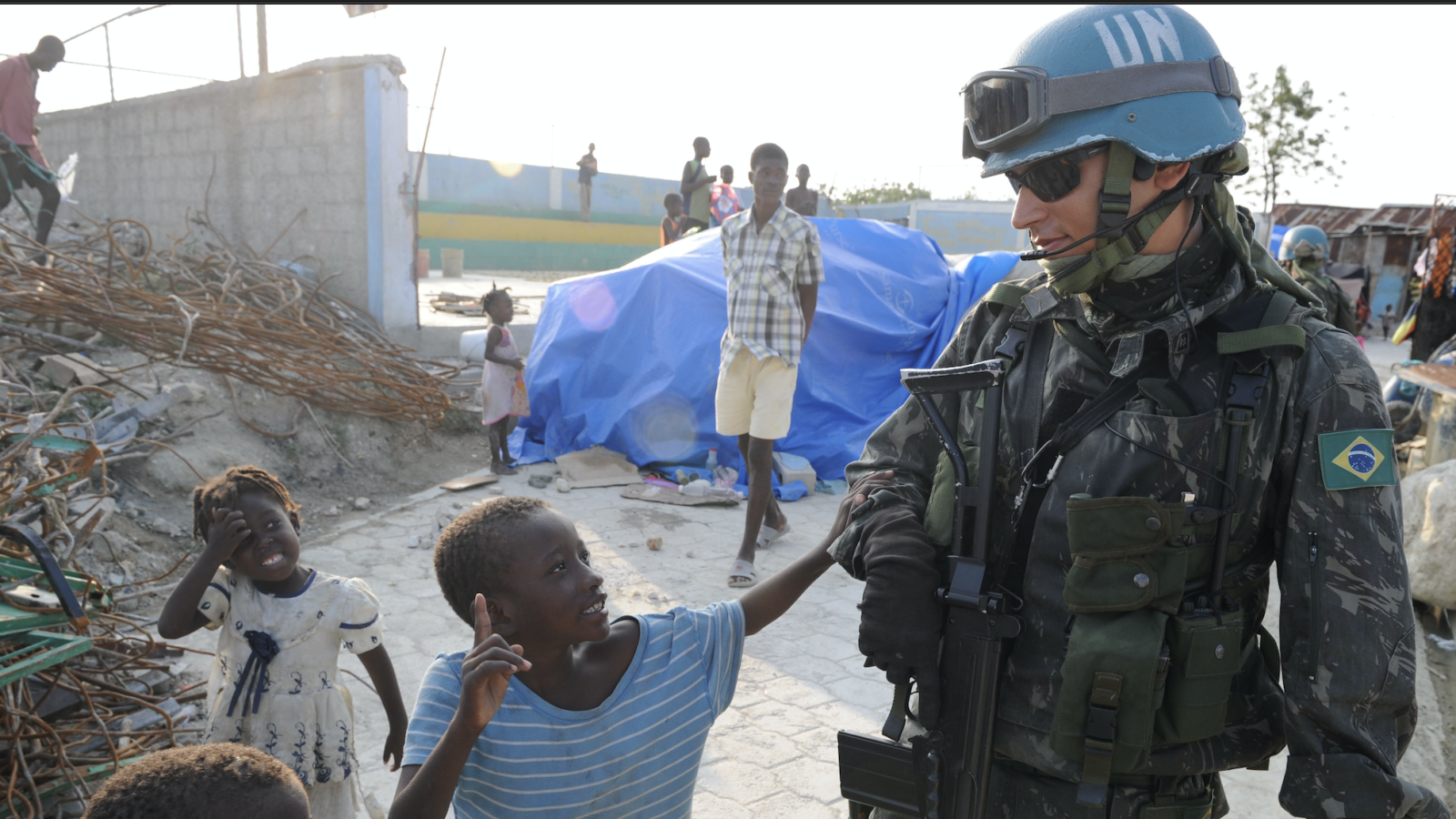 A tall male wearing a UN peacekeeper helmet says hello to some small children in Brazil.