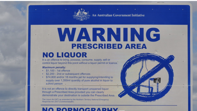 A government sign on a signpost in Australia that contains a warning about an alcohol prohibition in the area.