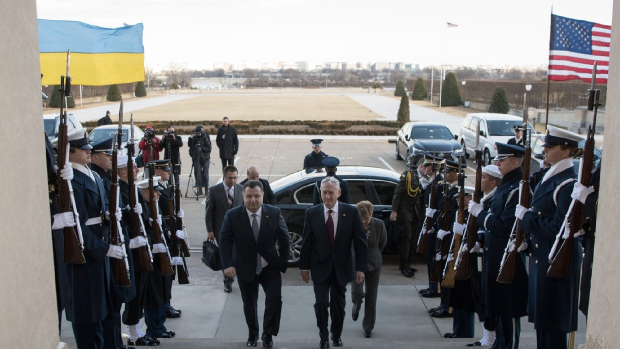 The U.S. and Ukranian Defense Secretaries walk up a set of stairs flanked by a row of U.S. soldiers.