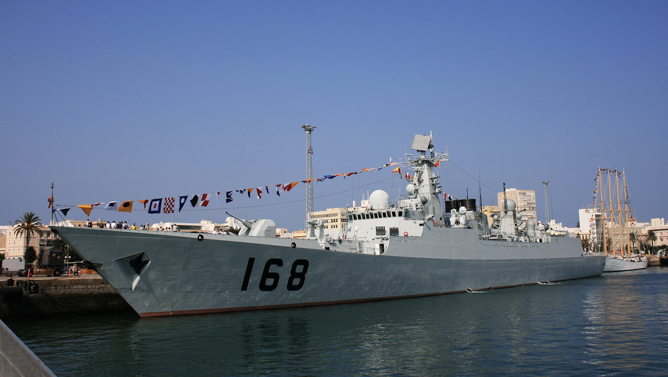 A large Chinese naval boat sits at a dock.