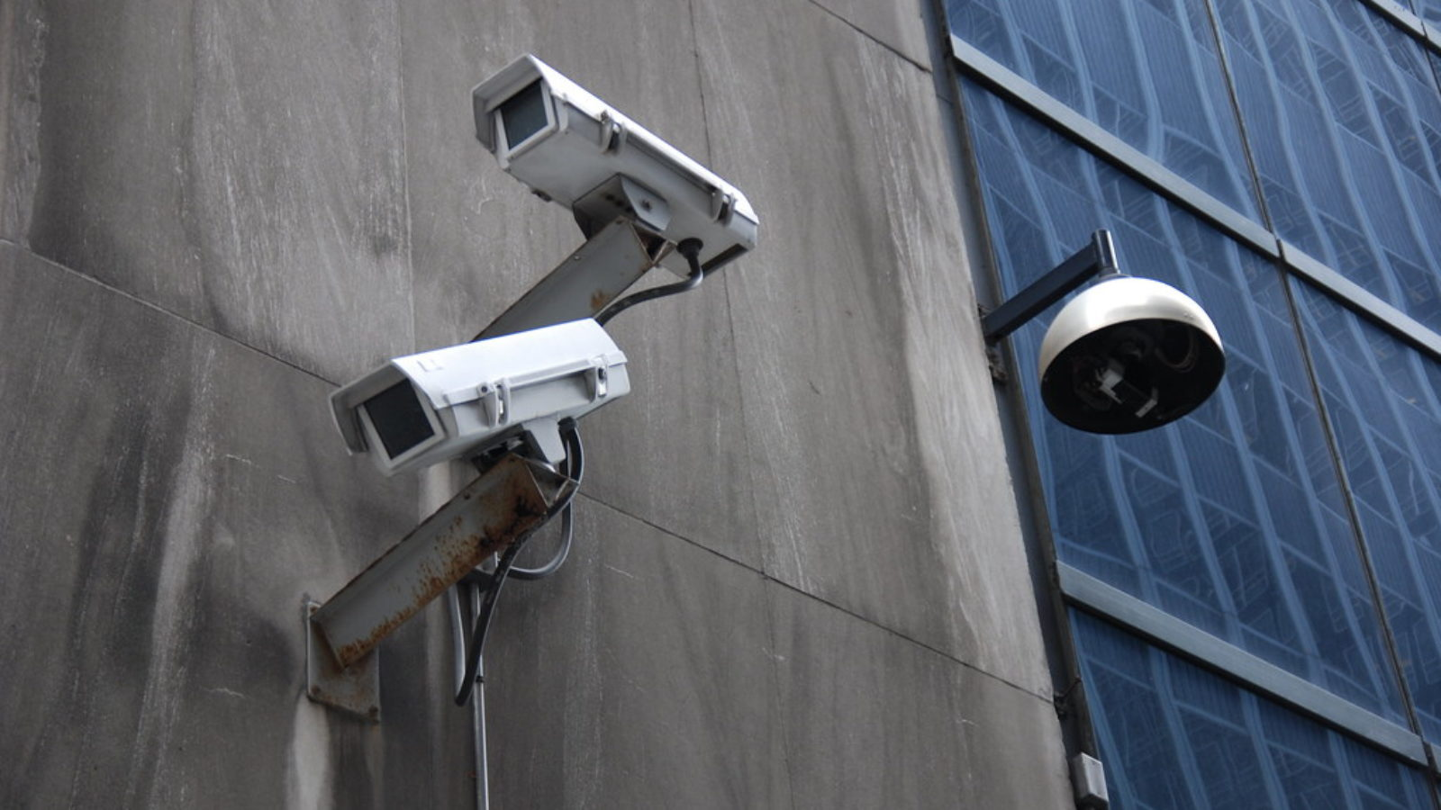 Two video surveillance cameras on the side of a building.