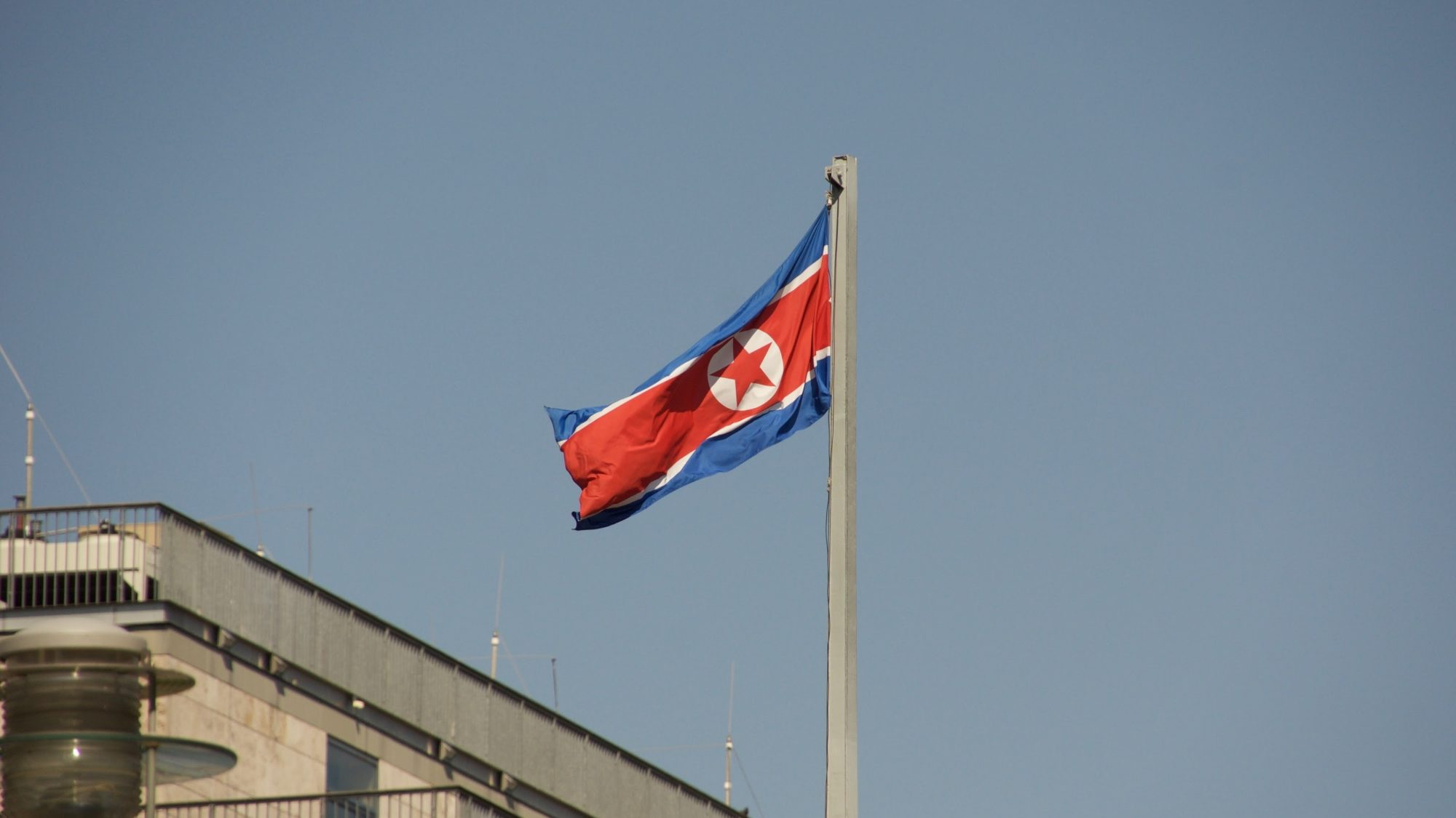 The flag of North Korea flies on a flagpole.