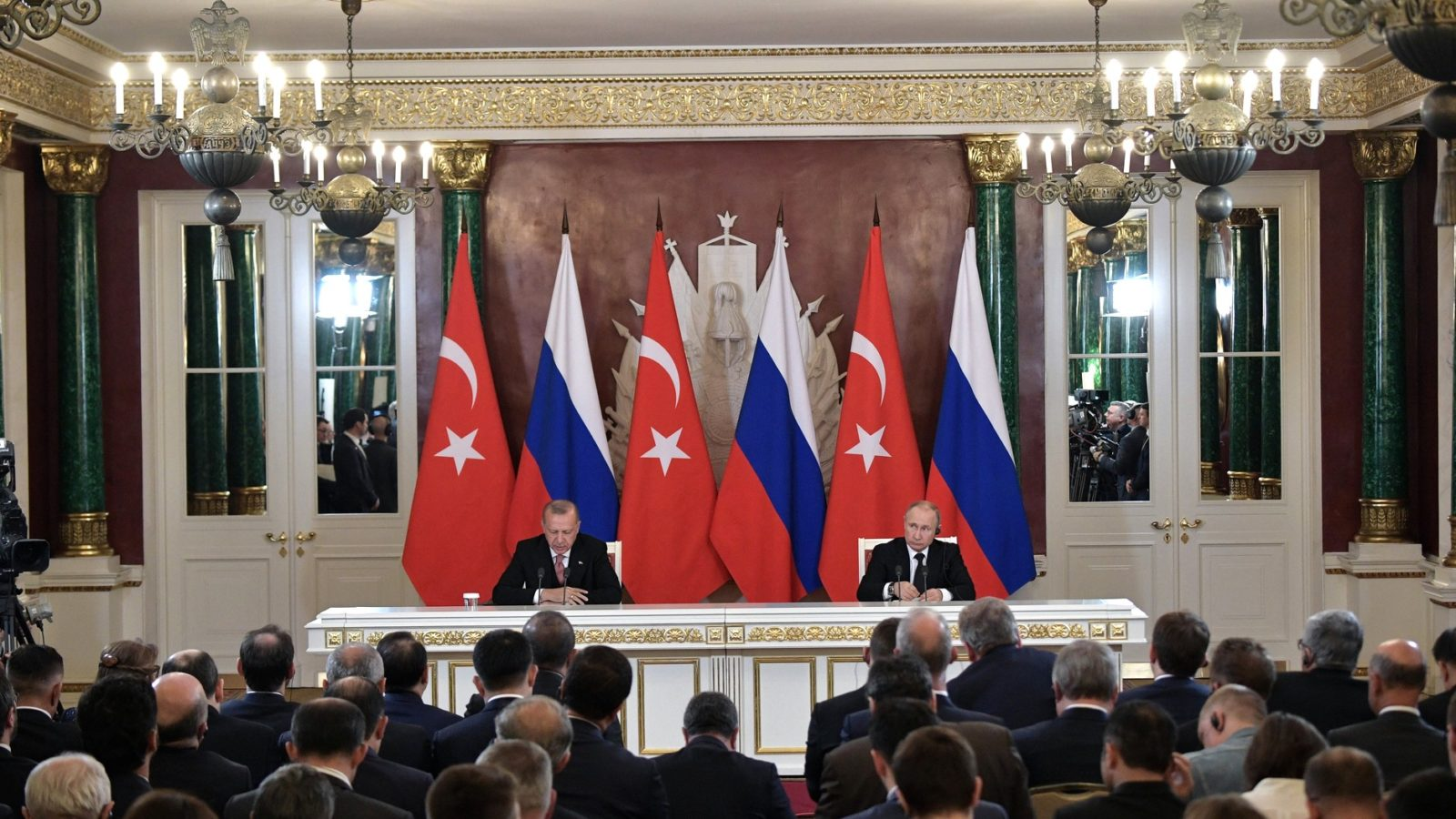 President Putin and President Erdogan sit at a table in front of the Turkish and Russian flags, in front of a room full of reporters.