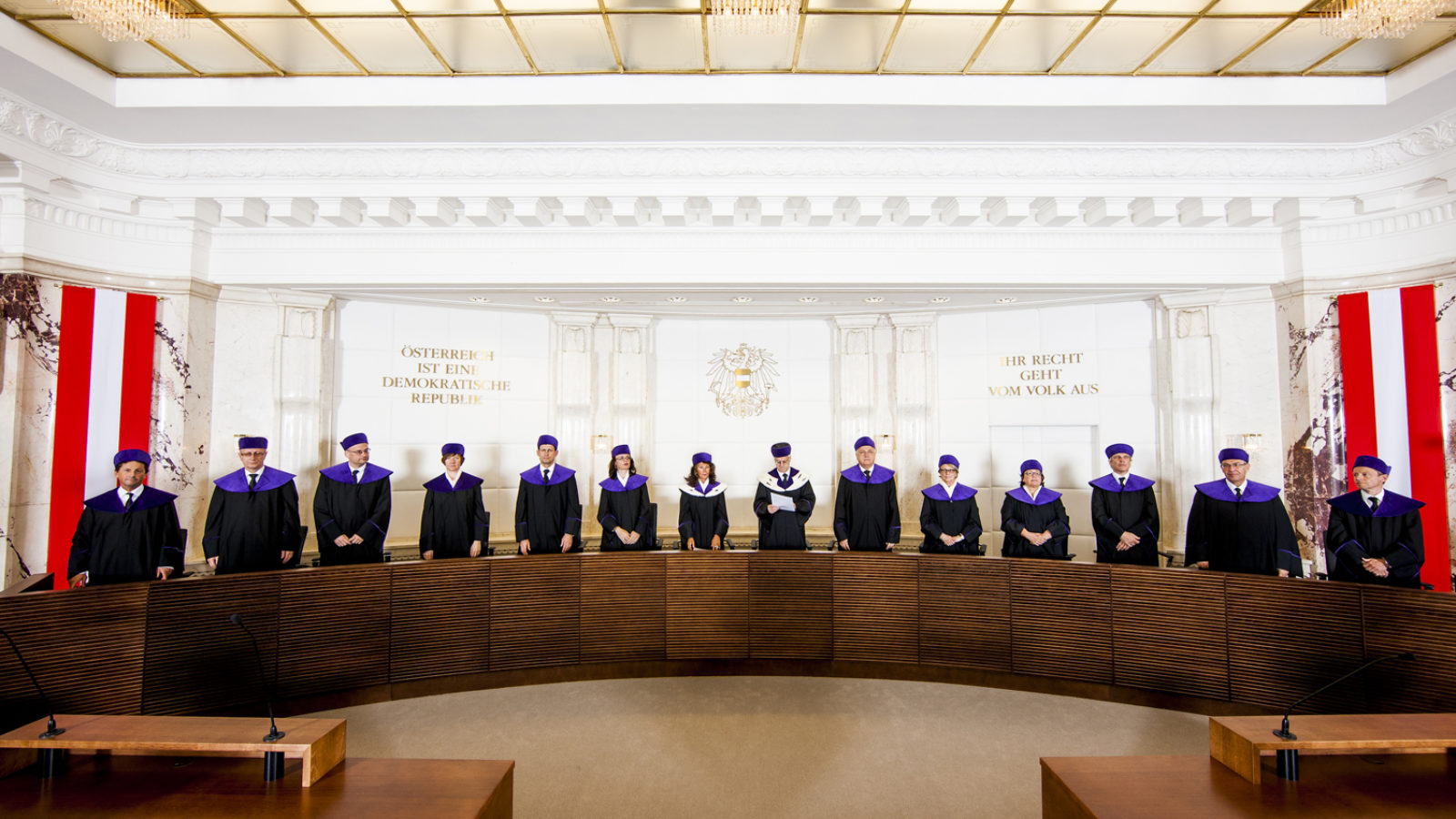Members of the Austrian constitutional court stand behind a long wooden table flanked by the Austrian flag.
