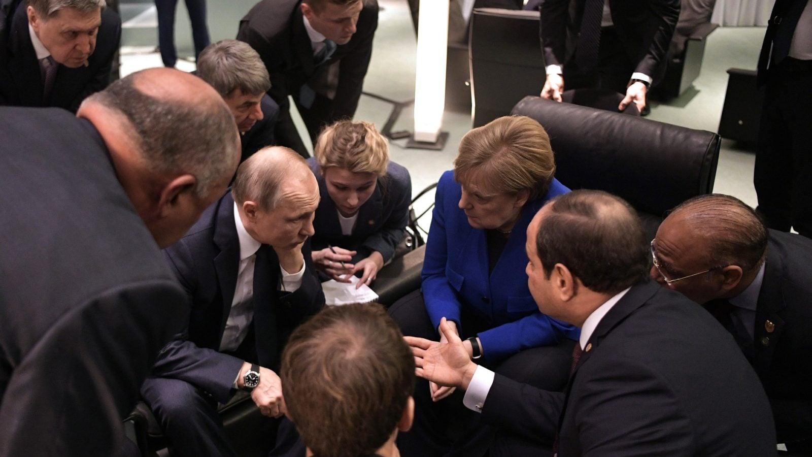 Angela Merkel, Emmanuel Macron, Vladimir Putin, and Abdel Fattah el-Sisi sit with their heads together.