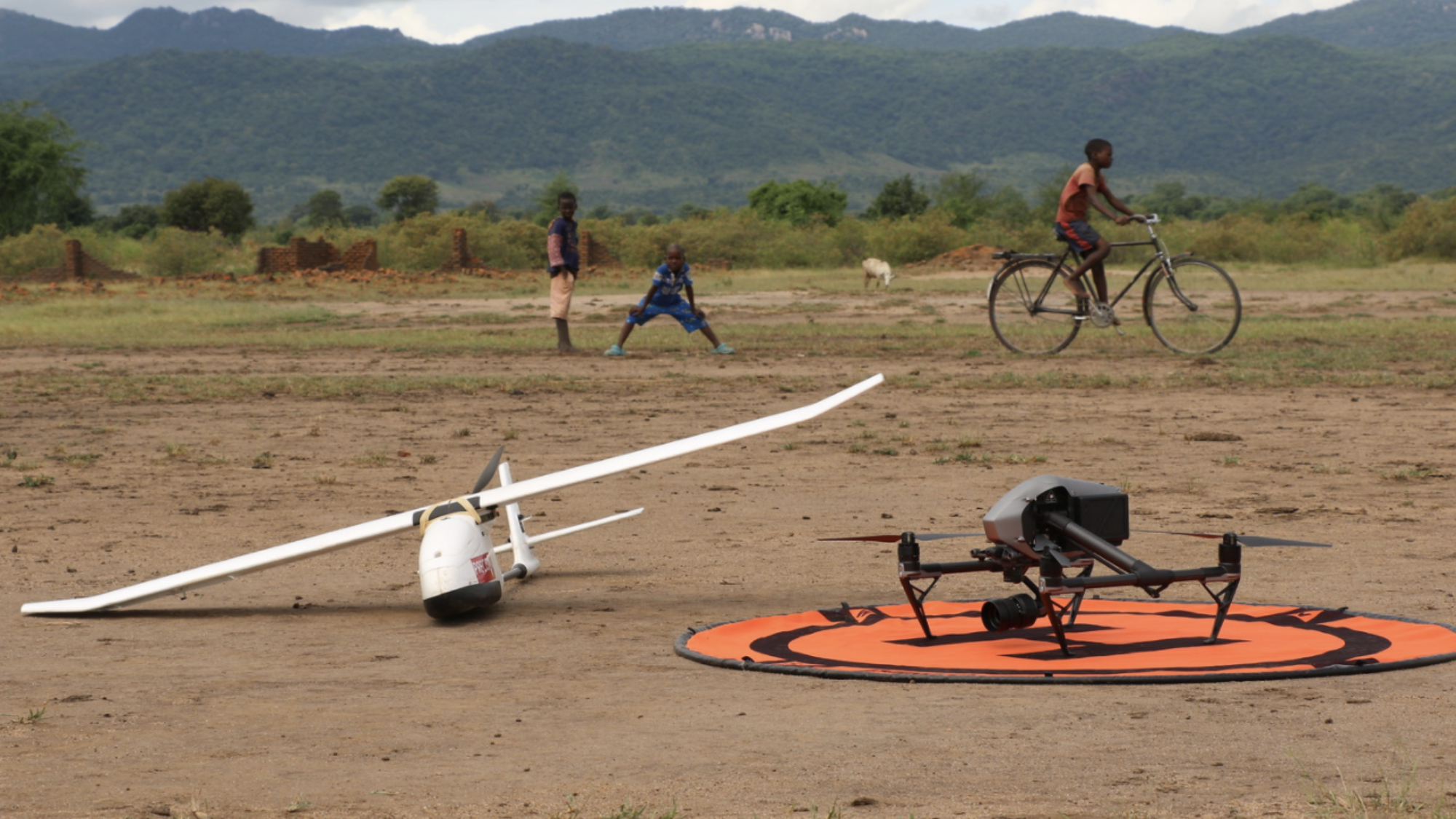 Two small drones sit rest on the dirt against the backdrop of mountains.