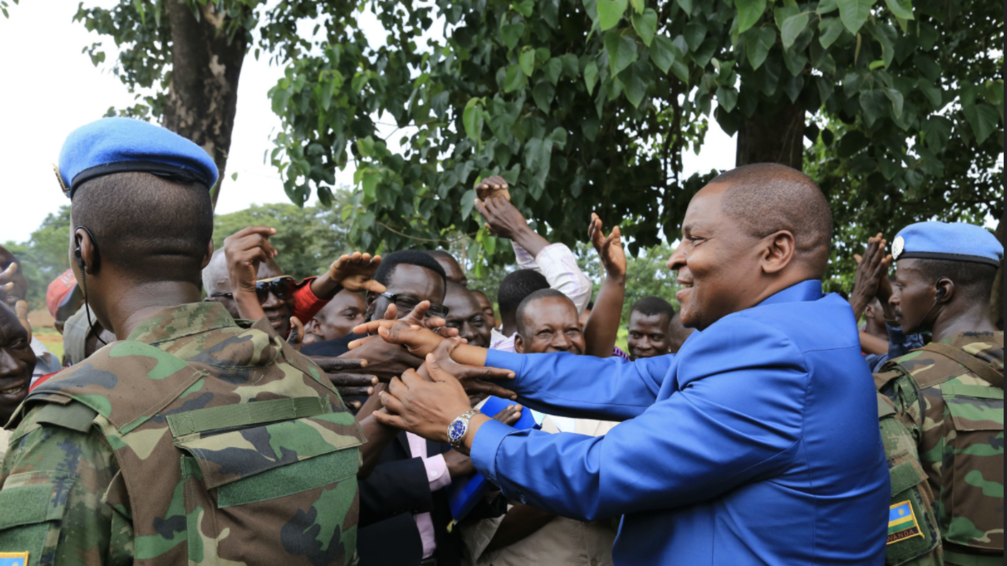 The president of the Central African Republic shakes hands with citizens alongside UN Peacekeepers.