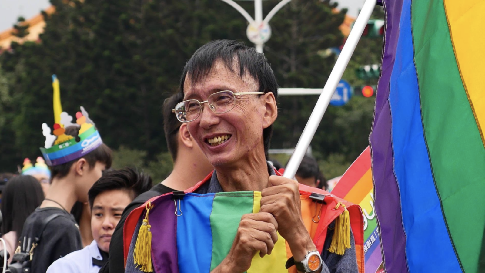 Activist Chi Chia-wei smiles holding a rainbow striped flag with a rainbow striped shirt.