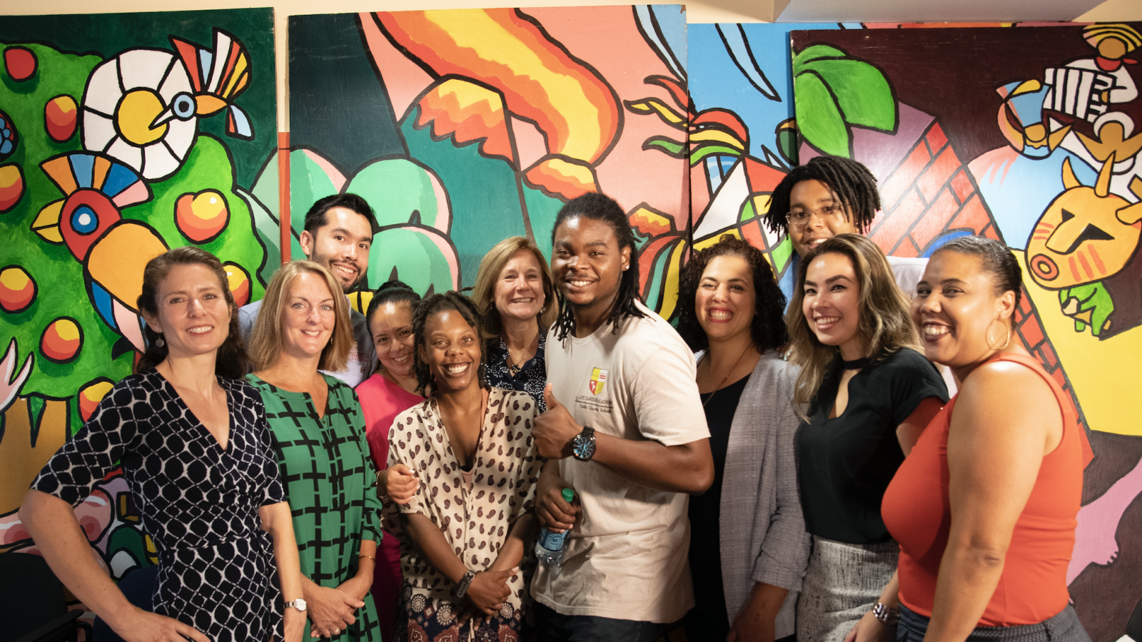 A group of people stand together smiling in front of a colorful mural.