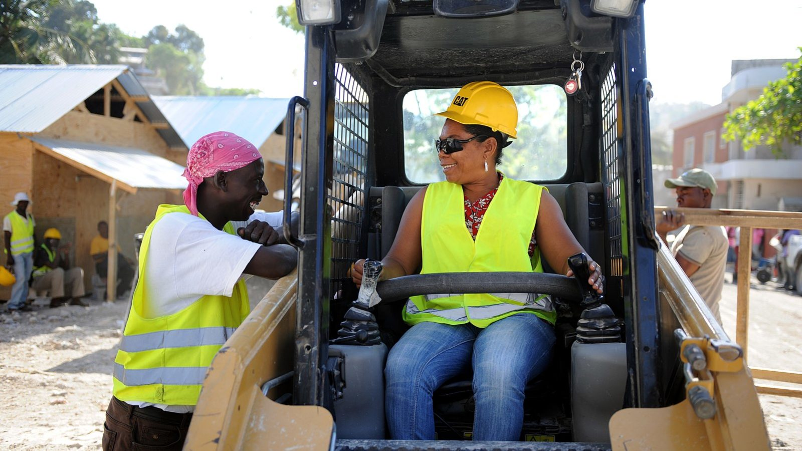 A woman operates heavy machinery to clear rubble in Haiti.