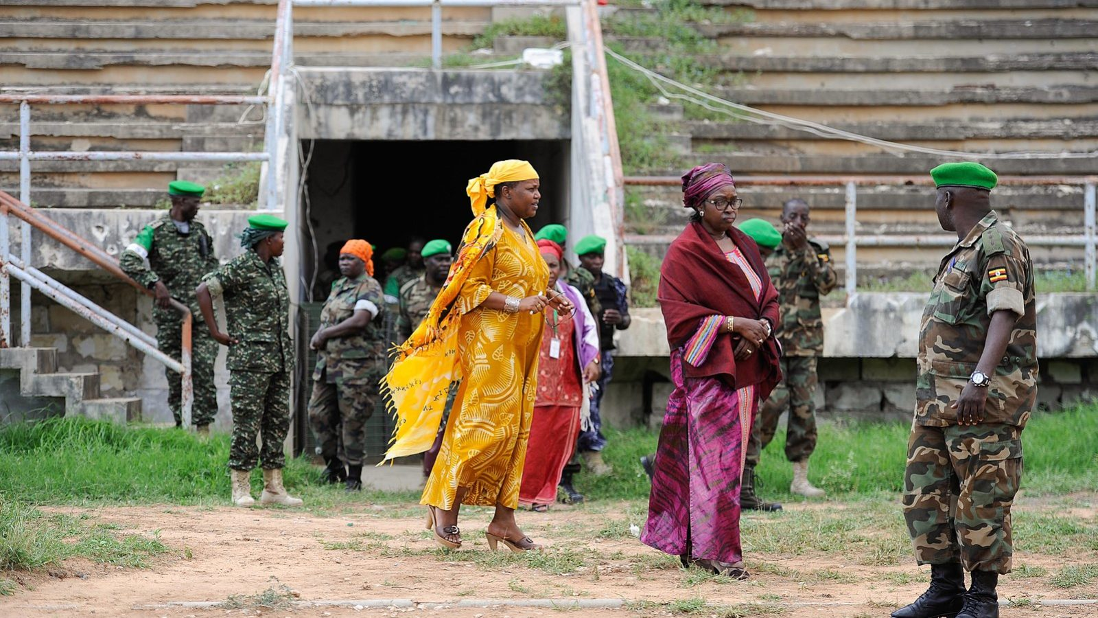 Three women in brightly colored clothing walk among soldiers in camouflage.
