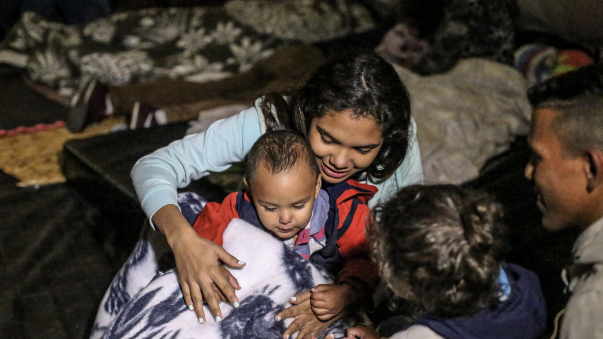 A Venezuelan mother and two of her children sit playing in a temporary shelter tent for migrants.