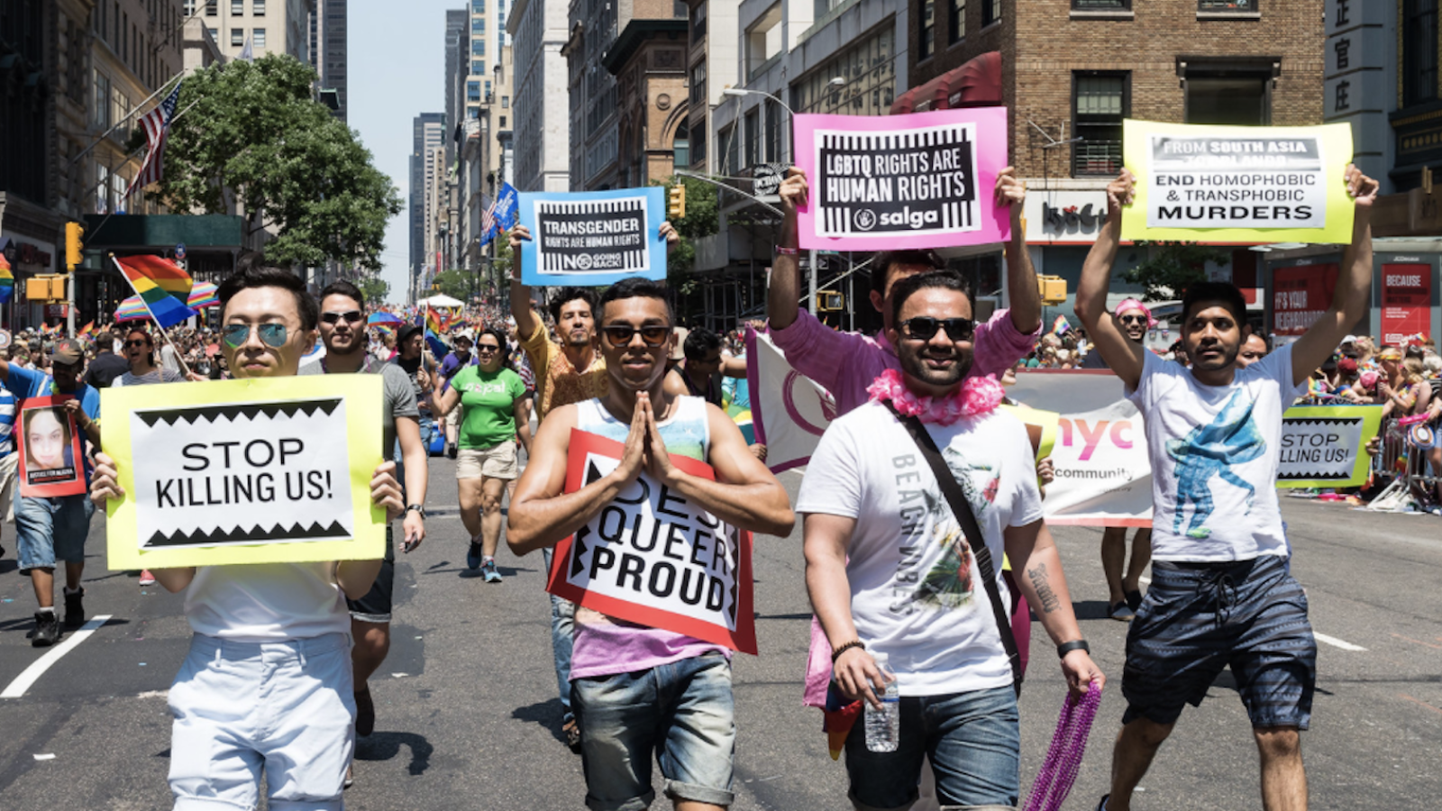 A group of men dressed in rainbow colors walk along a street, carrying signs with anti-homophobia messages.