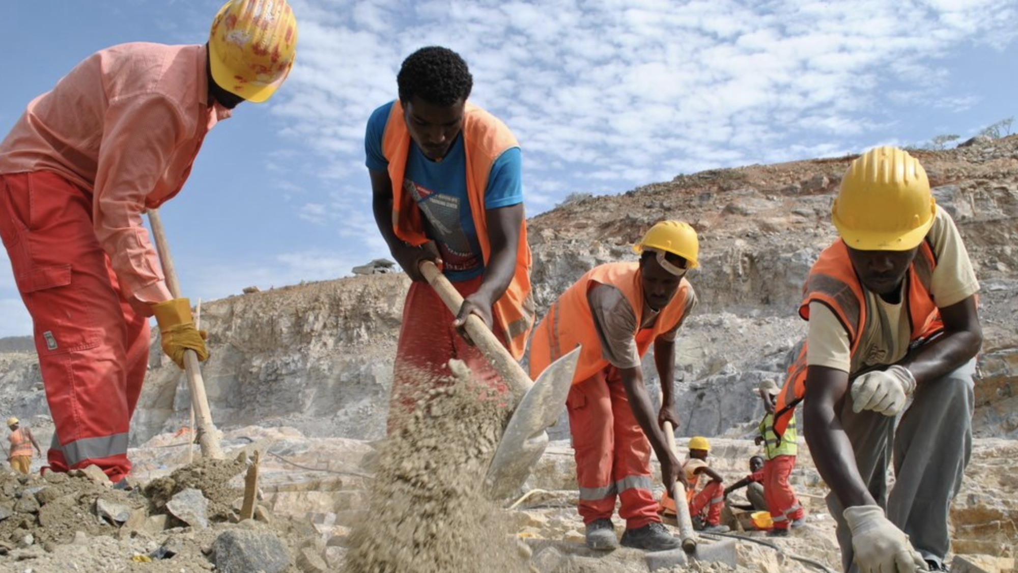 Several men wearing construction gear use tools to break ground for the GERD Dam in Ethiopia.
