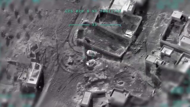 A gray image taken from Turkish drone footage showing buildings, terrain, and tanks from overhead.