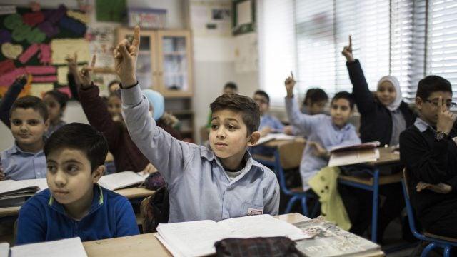 Students in Turkey raising their hands.