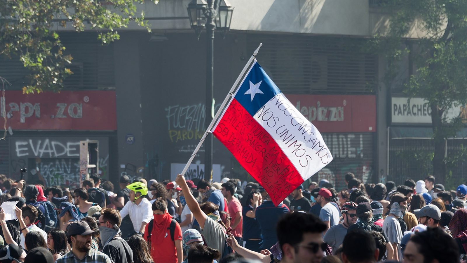 A Chilean flag is raised in the 2019 Protest in Santiago