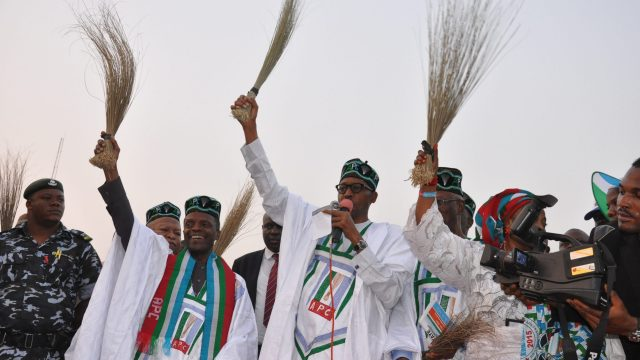 General Buhari holding a broom at a campign rally