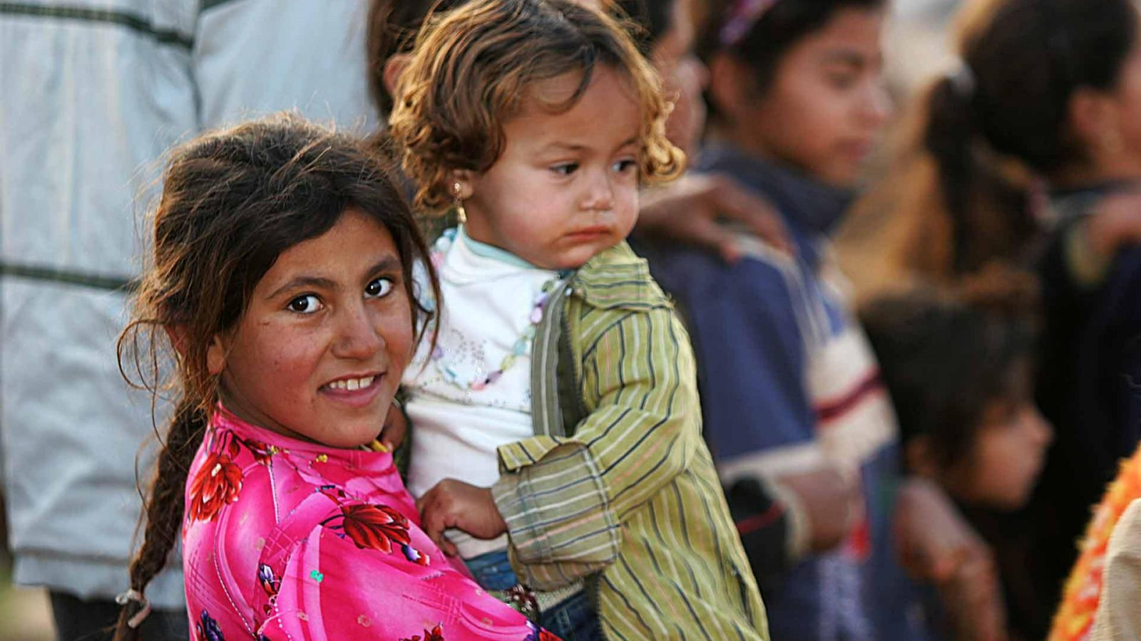 Young Iraqi refugee holding a young Iraqi refugee