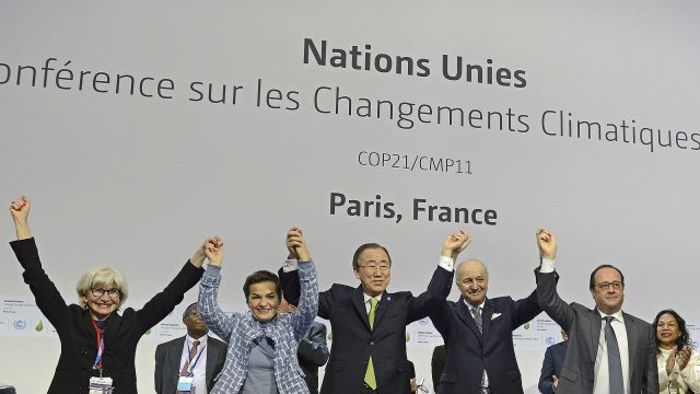 Participants of the plenary session of the COP21 for the adoption of the Paris Accord celebrate