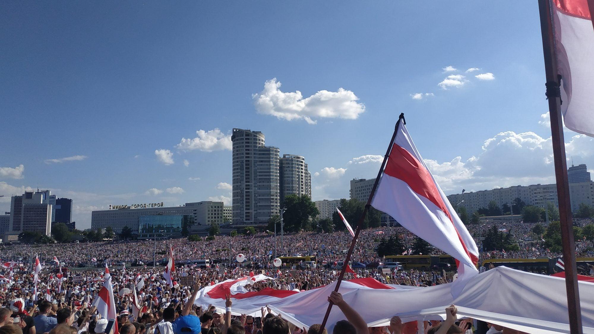 Protestors hold the Belarusian flag in Minsk