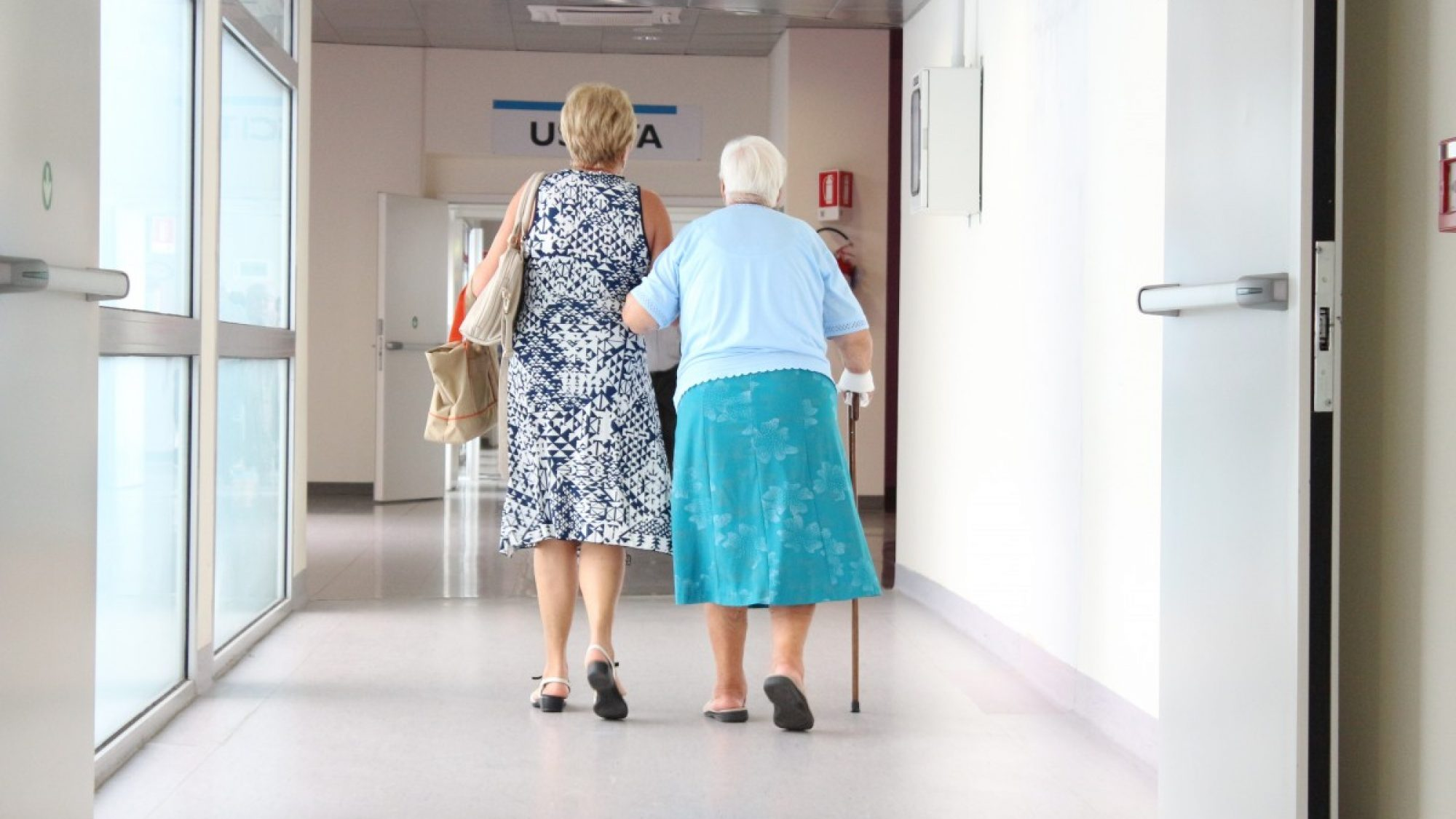 Elderly women walk down a hospital corridor