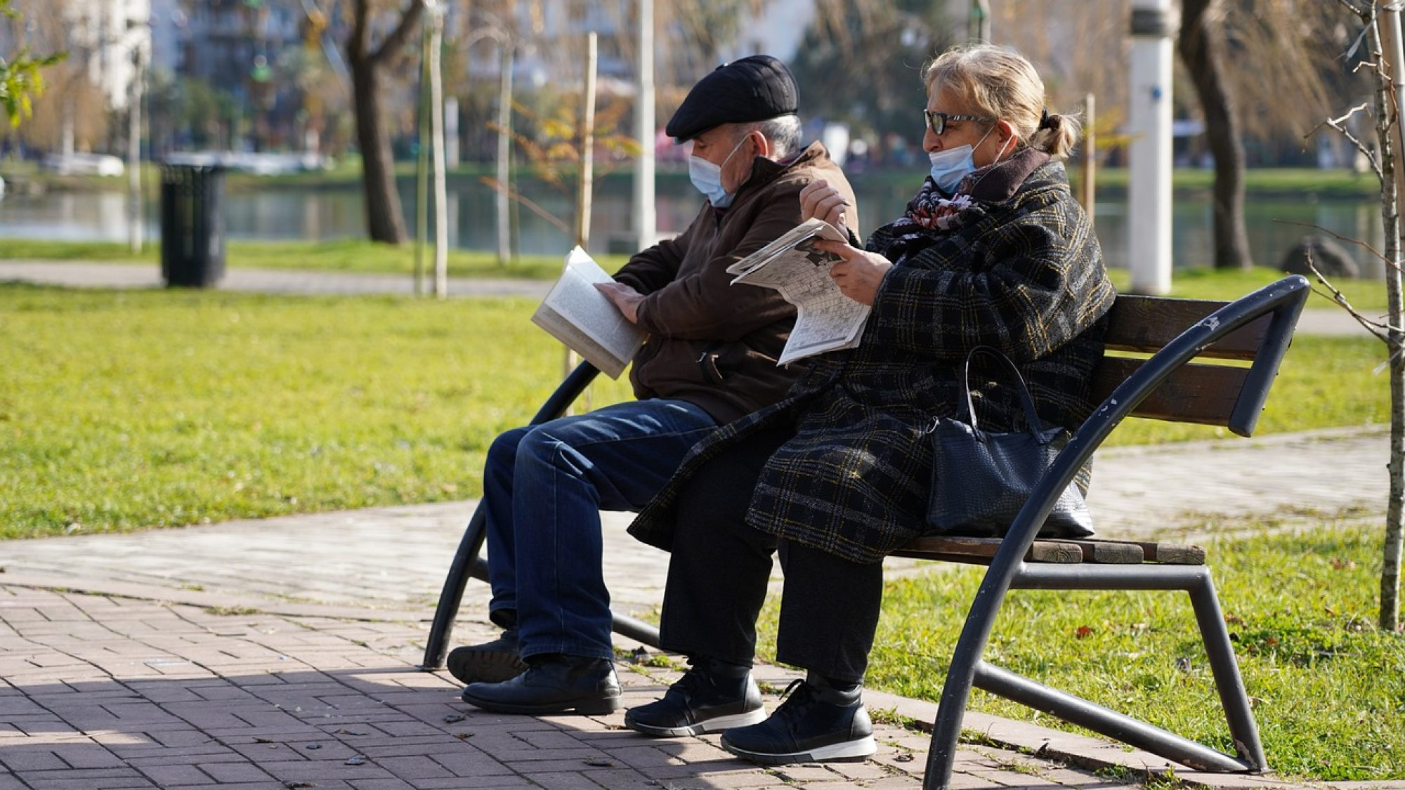 two elderly people with masks on sit on a bench outside